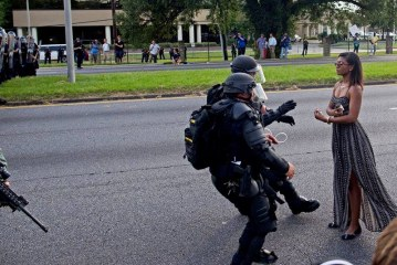 Photo of police in riot gear arresting protester in a dress strikes chord on social medi